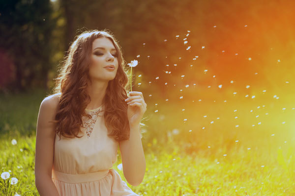 Beautiful young woman blowing dandelion. Trendy young girl at s